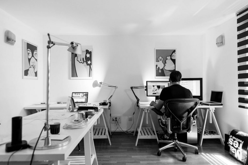 man sitting in small office on computer