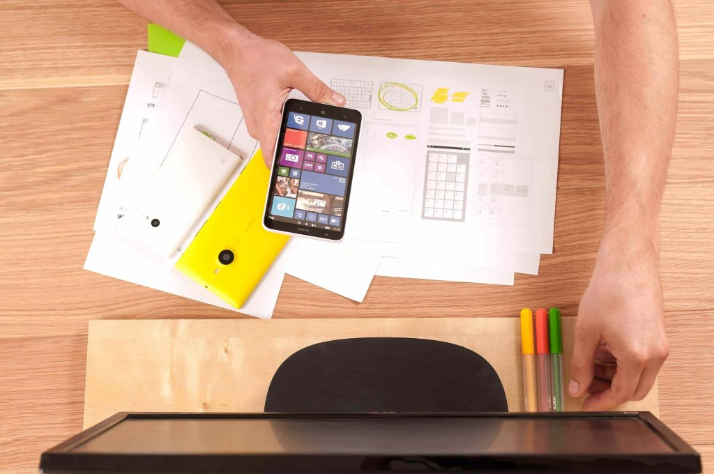 busy desk with blueprints and phones
